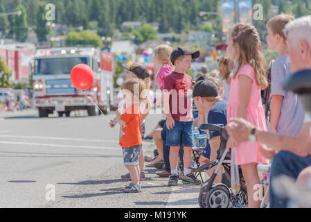 Children watch the parade floats drive by during the annual Stampede Parade in downtown Williams Lake. The stampede - Stock Photo