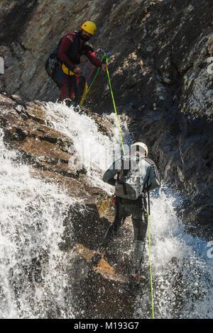 Men in wetsuits abseiling the Salto de Pino waterfall, by the Rio Caldares trail from Banos de Panticosa. Panticosa; - Stock Photo
