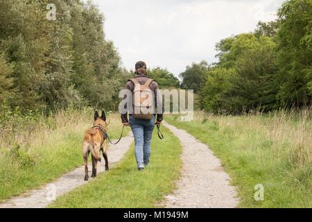 woman and her dog looking for houses. the discovery of abandoned buildings. post apocalypse. - Stock Photo