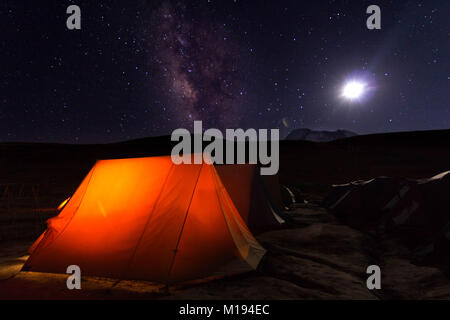 Moonlit night with milky way galaxy rising above our camp and tents in Ladakh - Stock Photo