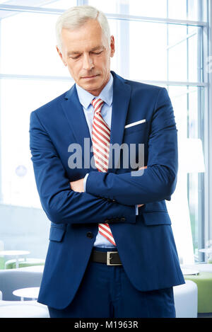 Shot of an careworn senior financial businessman standing at the office with arms crossed. - Stock Photo
