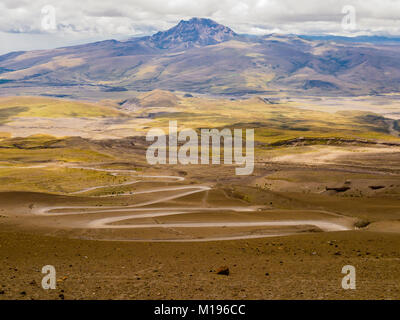 Impressive landscape with dirt winding road in Cotopaxi volcano national park, Ecuador - Stock Photo