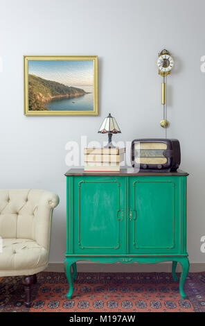 Interior shot of green vintage sideboard with old radio, stack of old books, and table lamp on background of off - Stock Photo