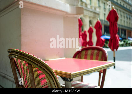 Typical table and rattan chairs on the terrace of a parisian outdoor cafe in the sunlight with parasols in the background. - Stock Photo