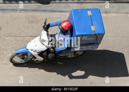 SAIGON, VIETNAM, DEC 17 2017, Delivery of consignments on motorbike. Motorcyclist rides with delivery in the large - Stock Photo