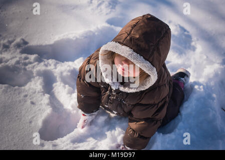 Looking down at a 3-year old toddler girl wearing a winter coat and sitting in the snow. - Stock Photo