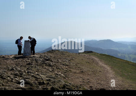 Malvern, UK - 29th March 2012: Two women examine the old trig point on Worcester Beacon on top of the Malvern Hills, - Stock Photo