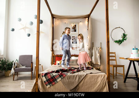 Children jumping on the bed in the children's room - Stock Photo
