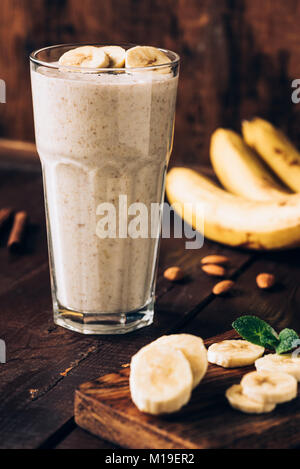 Banana smoothie in glass on brown wooden table. Healthy food, healthy eating concept - Stock Photo