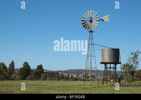 Windmill and tankstand in paddock, Queensland, Australia. Windmills are commonly used for pumping water from bores - Stock Photo