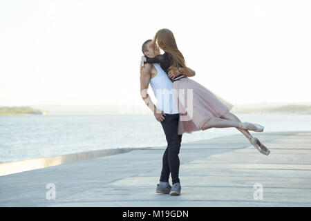 Slender ballerina dances with a modern dancer. Dating lovers. Passion and romance of dance. Performance in the streets - Stock Photo
