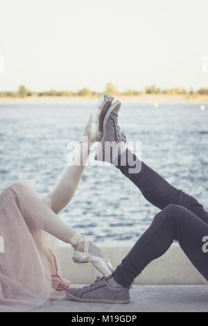Slender ballerina dances with a modern dancer. Dating lovers. Passion and romance of dance. Legs close-up. He is - Stock Photo