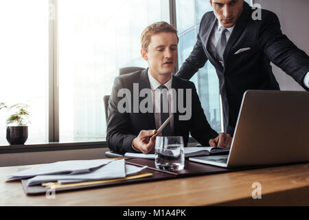 Corporate professionals working together on laptop. Two businessmen in office discussing business plan. - Stock Photo