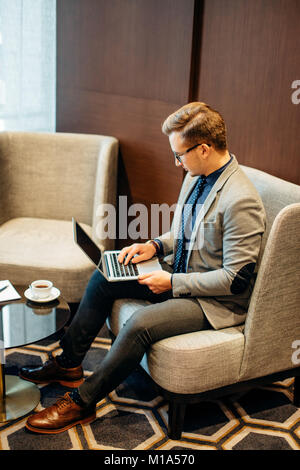 man works on laptop to business done early with cup of coffee - Stock Photo
