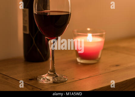 Red wine by candlelight. - Stock Photo