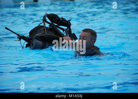 Spc. Benjamin Mason, Arizona, struggles along as he drags a 30-pound rucksack and dummy rifle the length of a pool. - Stock Photo