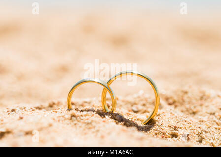 Two Golden Rings In Sand At Beach - Stock Photo