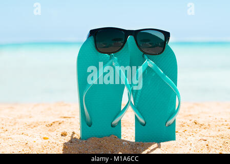Sunglasses Over The Turquoise Flip Flop On Sand At Beach In Summer - Stock Photo