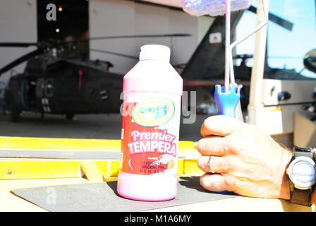 A bottle of fluorescent pink tempera paint is about to be used on a California Army National Guard UH-60 Black Hawk - Stock Photo