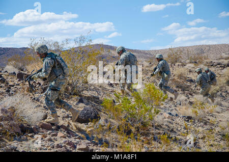 NTC FORT IRWIN - Soldiers with the 1st Battalion, 185th Armor Regiment (Combined Arms Battation) assault their objective - Stock Photo