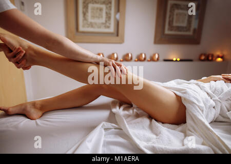 hands massaging human calf muscle.Therapist applying pressure on leg - Stock Photo