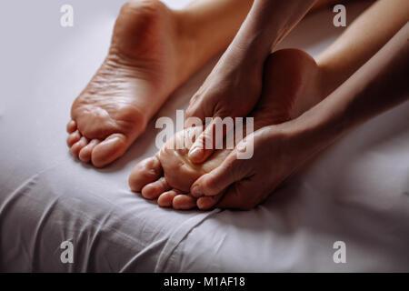 woman having feet massage in beauty salon, close up view - Stock Photo