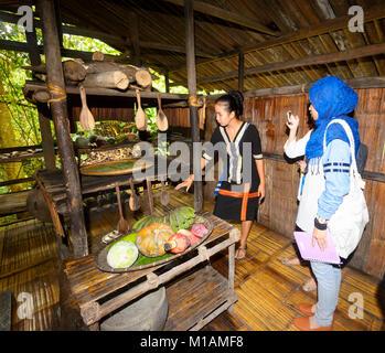 A young Malaysian woman tourist photographing a kitchen display at Mari Mari Cultural Village, Kota Kinabalu, Sabah, - Stock Photo