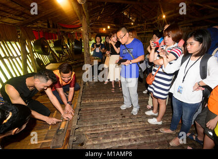 Chinese tourists watching young Malaysian men demonstrating how to make a fire in a traditional longhouse, Mari - Stock Photo