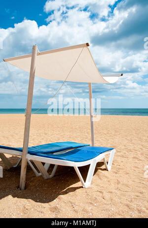 Sunbeds on an empty beach under clouded sky - Stock Photo