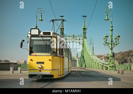 Historic tram on Freedom Bridge in Budapest, Hungary, on a bright day, toned image - Stock Photo