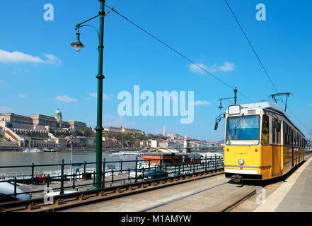 Historical tram runs on the riverside in Budapest with Buda Castle as a backdrop. A small picture of the castle - Stock Photo