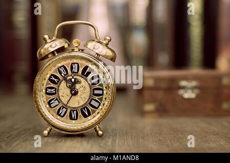 Vintage alarm clock showing five to twelve on the wooden table in study room. Happy New Year 2015!