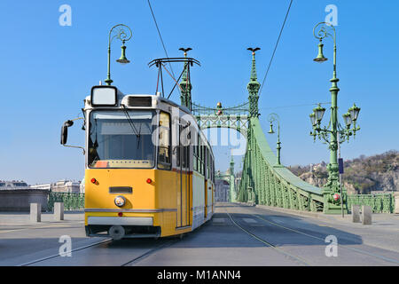 Historic tram on Freedom Bridge in Budapest, Hungary, on a bright day - Stock Photo