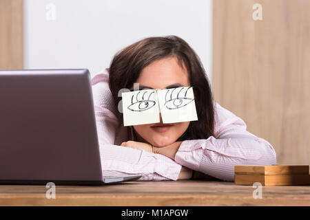 Sleeping Businesswoman Covering His Eyes With The Sticky Notes On Desk At Workplace - Stock Photo