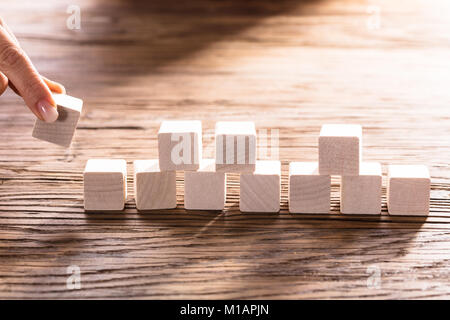 Close-up Of A Person Hand Arranging Blocks On Wooden Desk - Stock Photo