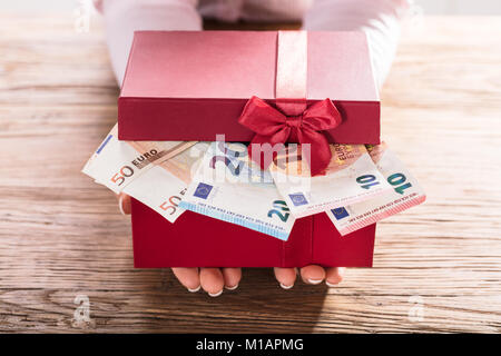 Close-up Of A Woman Holding Gift Box Of Euro Bills - Stock Photo