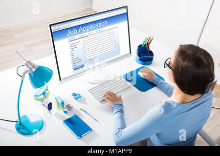 Elevated View Of A Businesswoman Feeling Job Application On Computer In Office - Stock Photo