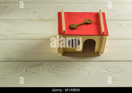 Model house with keyon the roof - Stock Photo