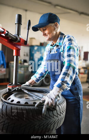 Senior female mechanic repairing a car in a garage. - Stock Photo