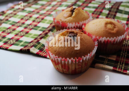 Homemade cakes baking on the kitchen table in paper molds - Stock Photo