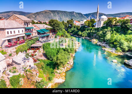 Mostar, Bosnia and Herzegovina. Morning sun on Nerteva River and Old City of Mostar, with Ottoman Mosque - Stock Photo