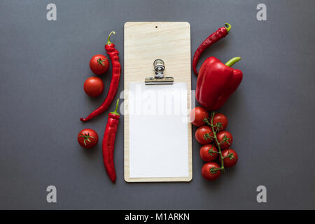 top view of fresh ripe red peppers and tomatoes with blank paper sheet on grey - Stock Photo