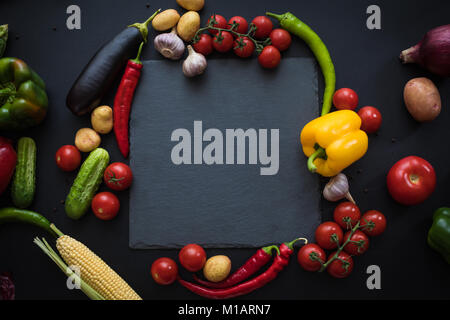 top view of various fresh ripe vegetables with slate board on black - Stock Photo
