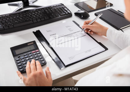 Close-up Of A Businesswoman Calculating Invoice Using Calculator On Desktop - Stock Photo