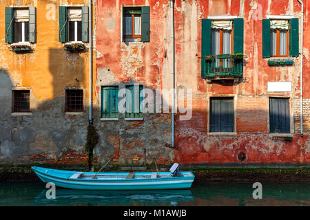 Boat on small canal moored against old colorful brick house in Venice, Italy. - Stock Photo