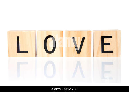 Light wood blocks with LOVE spelled out reflected on a white surface, isolated on white. Simple uncluttered design. - Stock Photo