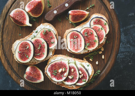 Fig and goat cheese toasts on wooden cutting board. Top view - Stock Photo