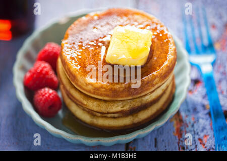 American pancakes with butter, maple syrup and raspberries - Stock Photo
