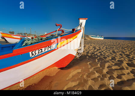 Colorful fishing boats lying in the sand at beach - Stock Photo