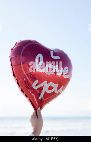 closeup of the hand of a young woman holding a red heart-shaped balloon with the text I love you written in it, - Stock Photo